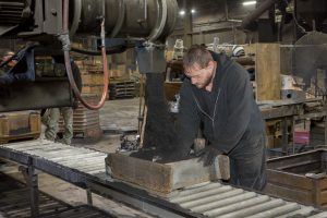 iron foundry worker working with molds